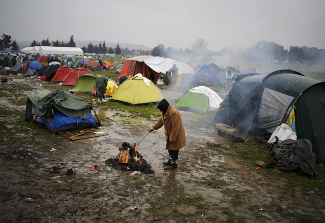 A migrant stands by a fire at a makeshift camp on the Greek-Macedonian border, near the village of Idomeni, Greece March 10, 2016. (Photo by Stoyan Nenov/Reuters)