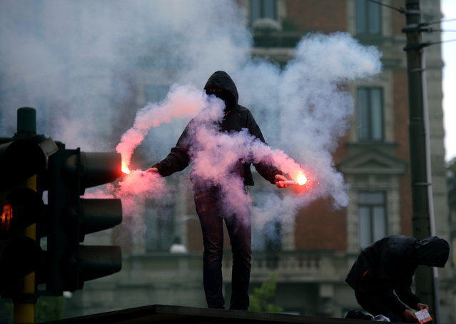Demonstrators wearing dark hood on their head, fire flares during a demonstration in downtown Milan on April 30, 2015 to protest against the World Exposition Milano 2015 (Universal Exposition) saying that the massively indebted Italian state should not be ploughing money into an ephemeral event at a time of economic hardship for many Italians. (Photo by Filippo Monteforte/AFP Photo)