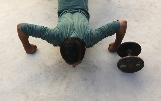 A participant does pushups in preparation for a local bodybuilding and fitness championship in Karachi, Pakistan March 13, 2016. (Photo by Akhtar Soomro/Reuters)