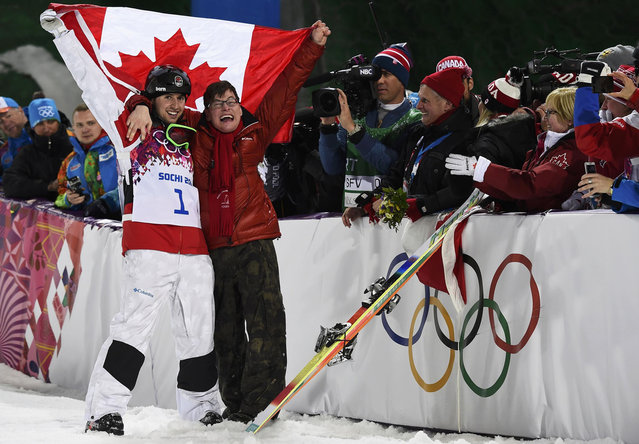 Winner Canada's Alex Bilodeau (L) and his brother Frederic celebrate with the Canadian flag after the men's freestyle moguls competition at the Sochi 2014 Winter Olympics in Rosa Khutor on February 10, 2014. (Photo by Dylan Martinez/Reuters)