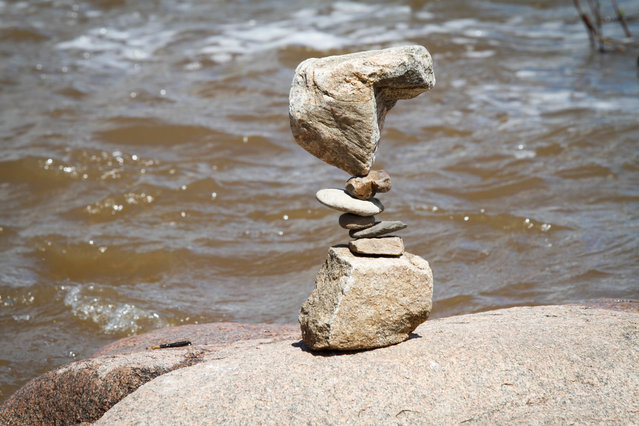 "Tim Anderson final balanced rock stack in the Llano River. Tim Anderson, rock balancing ""pro"" from Pennsylvania, carefully worked to balance his stack on a dry spot in the Llano river Saturday March 12, 2016. He was an honored guest of the festival and enjoyed visiting Texas so he came for another year. The river was higher this year because of the rains so the balancers could not get to the better rock that were available last year. (Photo by Nell Carroll/American-Statesman)"