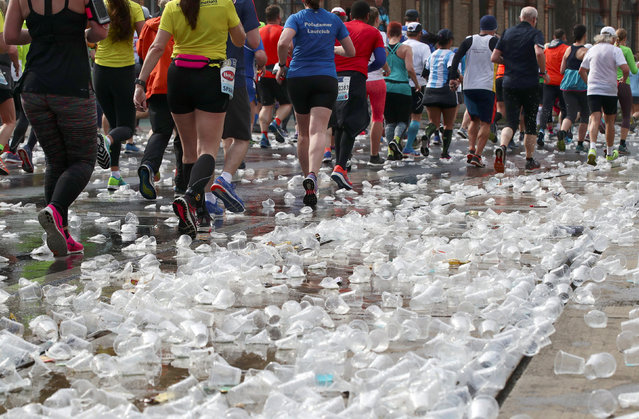 Runners pass along discarded cups at a refreshment point during the Vienna City Marathon in Vienna, Austria, April 7, 2019. (Photo by Lisi Niesner/Reuters)
