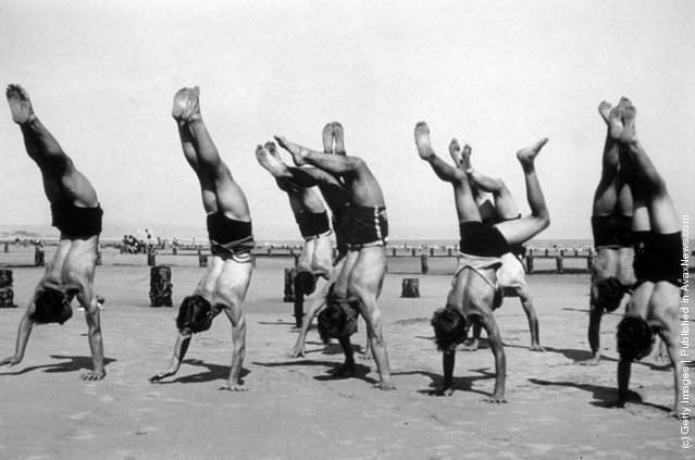 Boys doing handstands on the beach at a holiday camp, 1936