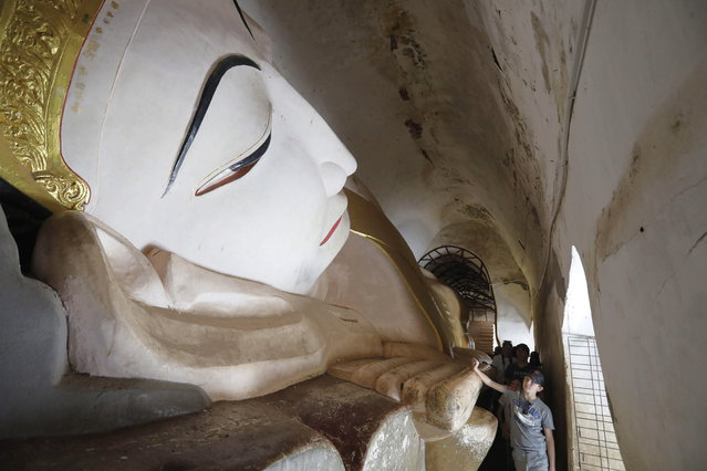 Foreign tourists inspect the large reclining Buddha statue inside Manuha Temple in Bagan, the ancient temple city of Myanmar, Mandalay region, Myanmar, 27 December 2018. Bagan, in the southwest of Mandalay, is located on a plain and features some 2,000 Buddhist temples, stupas and pagodas, which were constructed from the 11th to the 13th century. (Photo by Nyein Chan Naing/EPA/EFE)