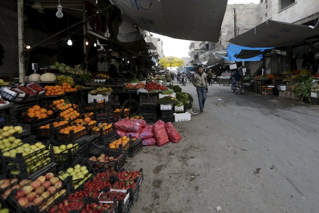 Residents walk through a vegetable market in the town of Marat Numan in Idlib province, Syria March 24, 2016. (Photo by Khalil Ashawi/Reuters)