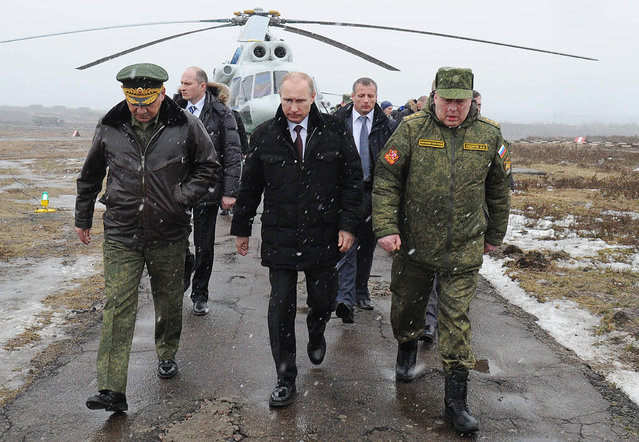Russian President Vladimir Putin, center, and Defense Minister Sergei Shoigu, left, and the commander of the Western Military District Anatoly Sidorov, right, walk upon arrival to watch military exercise near St.Petersburg, Russia, Monday, March 3, 2014. (Photo by Mikhail Klimentyev/AP Photo/RIA-Novosti/Presidential Press Service)
