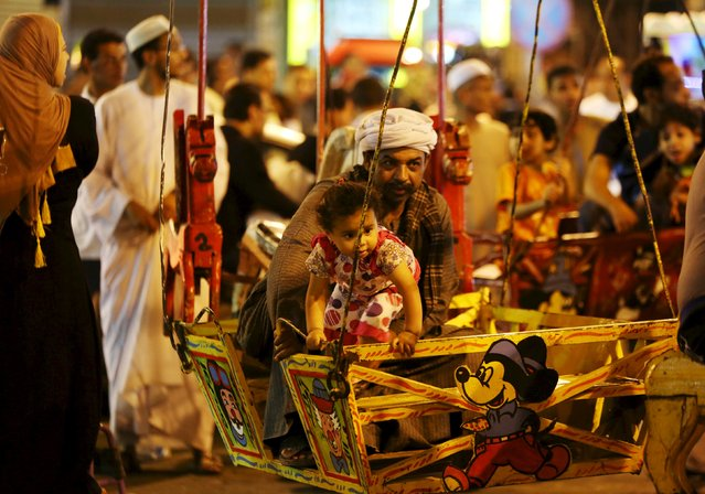 A father and his daughter rides a swing as people celebrate the birthday of Sayida Zeinab, the granddaughter of Prophet Mohammad, near her shrine in Cairo, May 13, 2015. (Photo by Mohamed Abd El Ghany/Reuters)