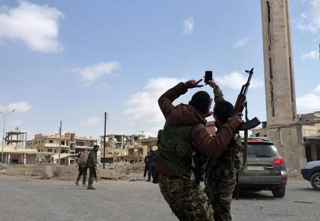 Syrian troops take a selfie as they walk in the damaged streets of the residential neighbourhoods in the modern town adjacent to the ancient Syrian city of Palmyra after they recaptured the UNESCO site from Islamic State (IS) group jihadists on March 27, 2016. Archaeologists were rushing to the ancient city of Palmyra on March 28, 2016 to assess the damage wreaked by the Islamic State group, after it was ousted by the Syrian army in a bloody battle. (Photo by Maher Al Mounes/AFP Photo)