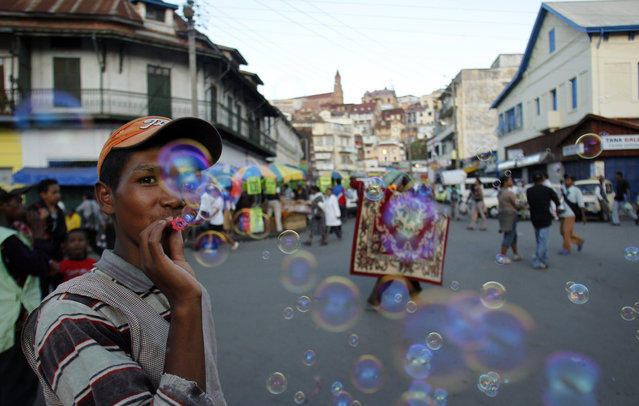 In this file photo taken Monday, November 22, 2010 a street hawker blows bubbles to attract customers in Antananarivo, Madagascar. (Photo by Themba Hadebe/AP Photo)