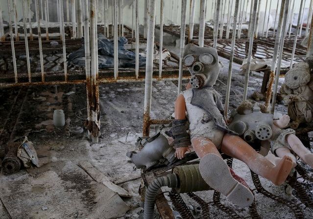 A doll in a children's gas mask is seen amongst beds at a kindergarten in the abandoned city of Pripyat near the Chernobyl nuclear power plant in Ukraine on March 28, 2016. (Photo by Gleb Garanich/Reuters)