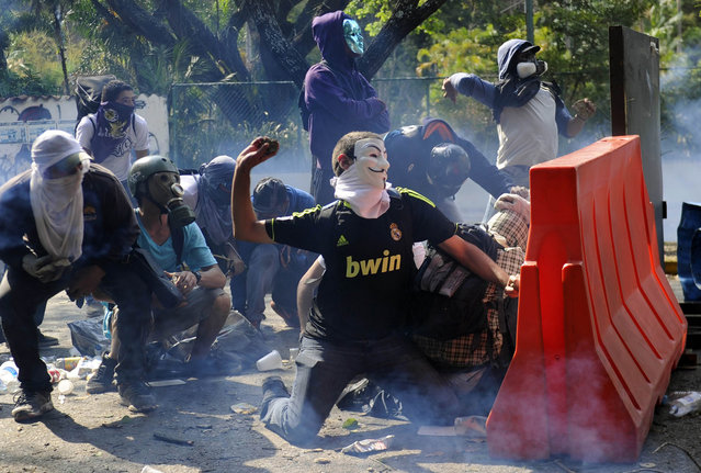 Venezuelan students clash with riot police during a protest against the government of President Nicolas Maduro, in Caracas on March 12, 2014. A young man was shot dead in a confused event during protests in the city of Valencia, in northern Venezuela. About 3,000 Venezuelan students marched Wednesday to mark a month since the first deaths in anti-government protests that have now claimed at least 22 lives. (Photo by Leo Ramirez/AFP Photo)