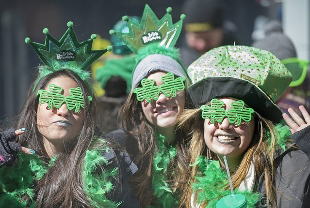 Spectators smile as the watch the annual St. Patrick's Day parade in Montreal, Sunday, March 16, 2014. (Photo by Graham Hughes/AP Photo/The Canadian Press)
