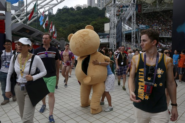Rugby Union, Hong Kong Sevens, Hong Kong Stadium on April 9, 2016: A fan hugs a man dressed as a teddy bear. (Photo by Bobby Yip/Reuters)