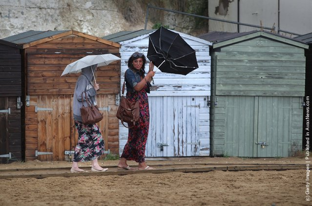 Women struggle with their umbrellas in high wind and rain on Viking Bay beach
