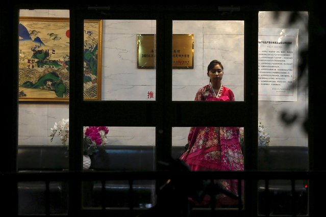 A woman wearing traditional costume waits for customers behind the doors of a North Korean restaurant in Beijing, China, April 12, 2016. (Photo by Damir Sagolj/Reuters)
