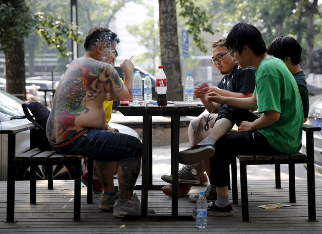 A tattooed man plays a poker game with his friends in Beijing, China, May 25, 2015. (Photo by Kim Kyung-Hoon/Reuters)