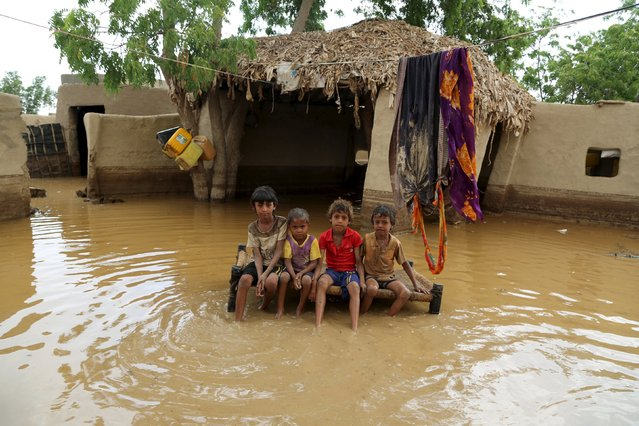Children sit on a bed in a flooded house following heavy rain in a village in Yemen's Red Sea province of Houdieda April 15, 2016. (Photo by Abduljabbar Zeyad/Reuters)