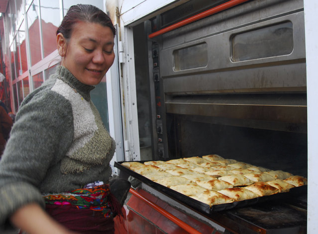 A woman cooks pastry at the Jygerluk market on the outskirts of Ashgabat, February 8, 2007. (Photo by Michael Steen/Reuters)