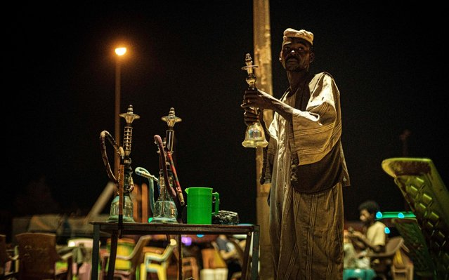 A Sudanese man prepares waterpipes at an open cafe near the Nile in Khartoum, on June 14, 2019. (Photo by Yasuyoshi Chiba/AFP Photo)