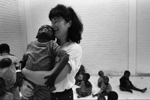 Mary Dunne, a nurse with the Irish aid agency Concern, hugs an unaccompanied child at a transit camp in Gisenyi, Rwanda; 1996. Aid agencies took care of hundreds of children without parents upon their arrival in Rwanda amongst the hundreds of thousands of returning refugees. (Photo by Carol Guzy/The Washington Post)