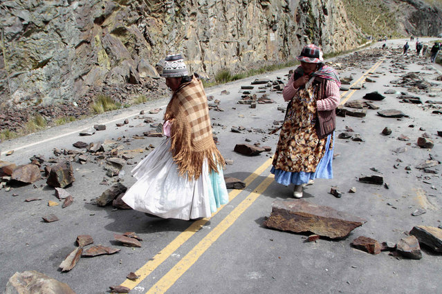 Women walk on a road blocked by independent miners in the La Cumbre mountain pass near La Paz, Bolivia, on April 1, 2014. Thousands of independent miners are blocking the main routes along Bolivia to reject a new mining law by President Evo Morales' government, which they say prevents them from associating with private mining firms of their choice. (Photo by David Mercado/Reuters)
