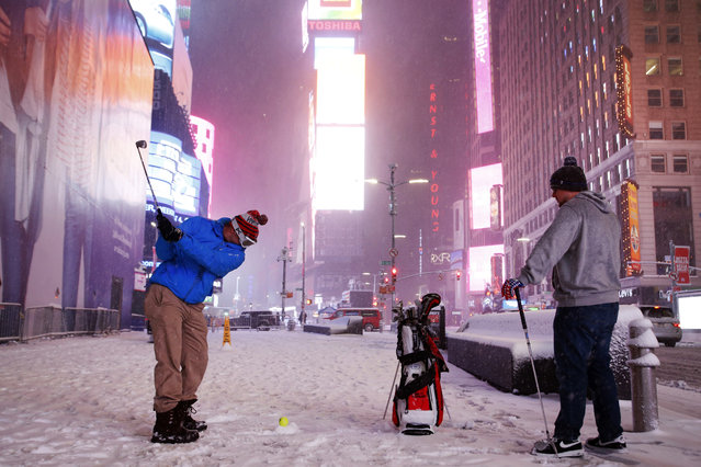 Two men play golf with a tennis ball as a snowstorm sweeps through Times Square, Tuesday, March 14, 2017, in New York. (Photo by Mark Lennihan/AP Photo)
