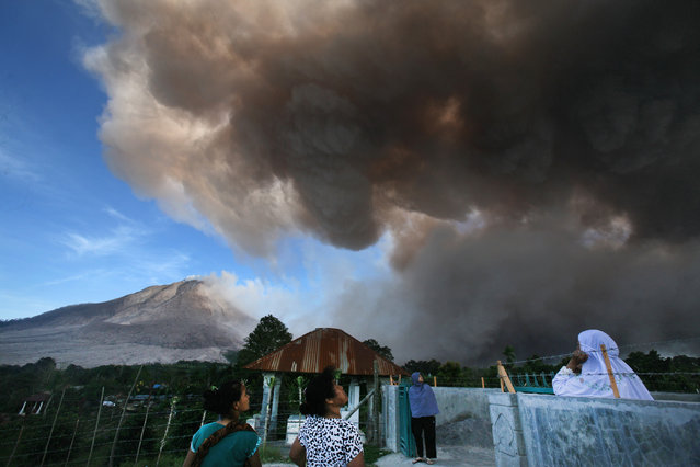 Villagers watch as Mount Sinabung releases volcanic material into the air in Tiga Serangkai, North Sumatra, Indonesia, Thursday, June 25, 2015. The volcano has spewed hot lava almost daily since its alert status was raised early this month to the highest level. Thousands of villagers whose homes are in the danger zone have been evacuated since then to safer areas. (Photo by Binsar Bakkara/AP Photo)