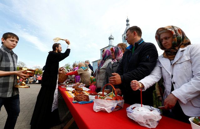 "An Orthodox priest sprinkles holy water on believers and their ""paskha"" cakes, eggs and other food on the eve of Orthodox Easter outside the church in the town of Bobruisk, Belarus, April 30, 2016. (Photo by Vasily Fedosenko/Reuters)"