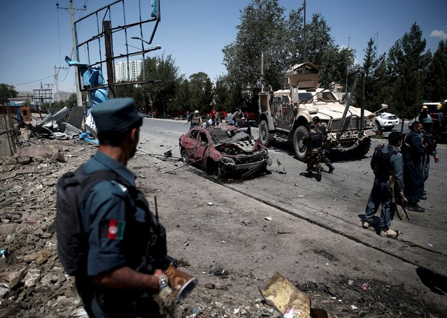 An Afghan policeman keeps watch at the site of a suicide bomb attack in Kabul, Afghanistan June 30, 2015. (Photo by Ahmad Masood/Reuters)