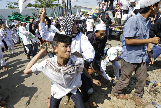 A man throws a rock at police officers during a Muslim hardliner protest against the construction of a Catholic church in Bekasi, Indonesia, Friday, March 24, 2017. Indonesian police fired tear gas to disperse the protesters as they tried to force their way into the Santa Clara church, which has been under construction since November. (Photo by Achmad Ibrahim/AP Photo)