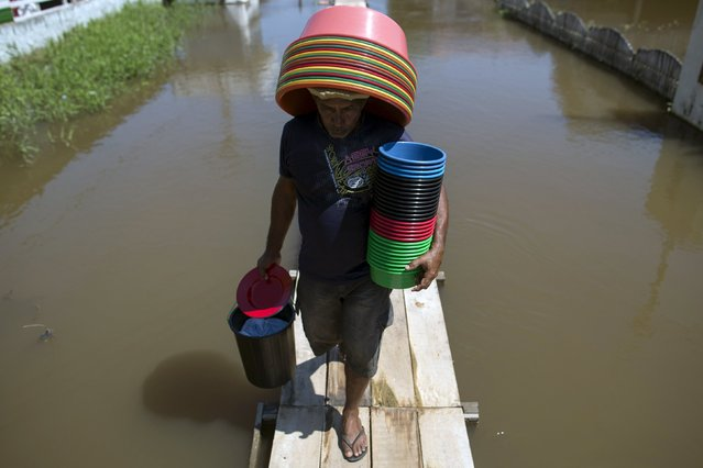 A vendor walks on a makeshift walkway above a flooded street from the rising Rio Solimoes, one of the two main branches of the Amazon River, in Careiro da Varzea of Amazonas State, Brazil, June 30, 2015. (Photo by Bruno Kelly/Reuters)