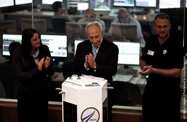 Israeli President Shimon Peres (centre) and Space IL engineers introduce the new prototype nano spaceship during a press conference on December 8, 2011 in Ehud, Israel