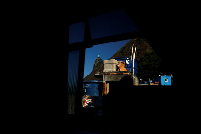 Christ the Redeemer statue is seen through a window of Scene hostel in Santa Marta favela, in Rio de Janeiro, Brazil, April 24, 2016. (Photo by Pilar Olivares/Reuters)