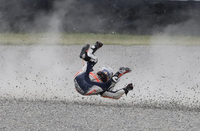 Spain's Dani Pedroza rolls on the gravel after he fell off his Honda during Argentina's Motorcycle Grand Prix at the Termas de Rio Hondo circuit in Argentina, April 9, 2017. (Photo by Natacha Pisarenko/AP)