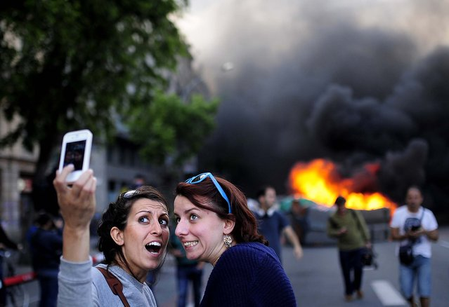 "Tourists take a ""selfie"" as demonstrators burn a trash container during a May Day rally in Barcelona, Spain, on May 1, 2014. Tens of thousands of workers marked May Day in European cities with a mix of anger and gloom over austerity measures imposed by leaders trying to contain the eurozone's intractable debt crisis. (Photo by Manu Fernandez/Associated Press)"