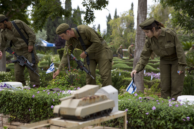 Israeli soldiers place small flags with black ribbons on the grave of fallen soldiers on the eve of memorial Day in Kiryat Shaul military cemetery in Tel Aviv, Israel, Tuesday, May 10, 2016. (Photo by Ariel Schalit/AP Photo)