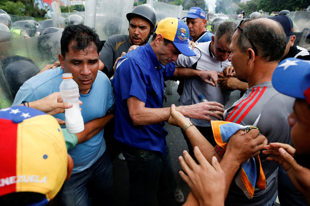 Venezuelan opposition leader and Governor of Miranda state Henrique Capriles (C) recovers from tear gas after clashes with riot policemen during a rally to demand a referendum to remove President Nicolas Maduro in Caracas, Venezuela, May 11, 2016. (Photo by Carlos Garcia Rawlins/Reuters)