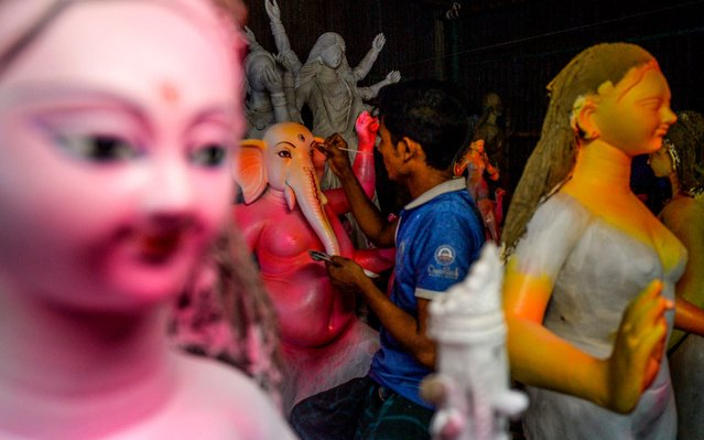 "A young artist works on a clay idol of the Hindu goddess Durga in preparation for the upcoming Hindu festival ""Durga Puja"" in Old Dhaka on September 18, 2019. (Photo by Munir Uz Zaman/AFP Photo)"