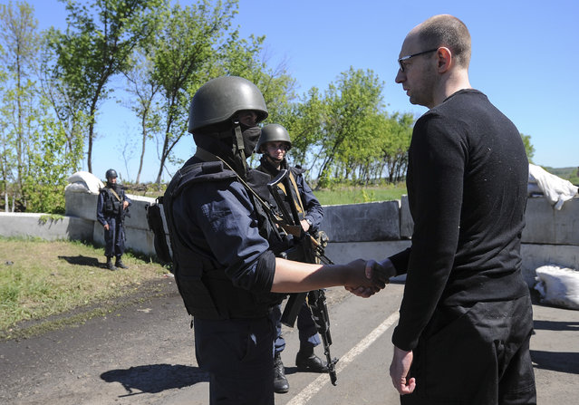 Ukrainian Prime Minister Arseniy Yatsenyuk, right, shake hands with Ukrainian soldiers at a block post on the road at Slovyansk, Ukraine, Wednesday, May 7, 2014. Ukrainian military operations that began Monday to expunge pro-Russia forces from the city of Slovyansk were the interim government's most ambitious effort so far to quell weeks of unrest in Ukraine's mainly Russian-speaking east. (Photo by Andrew Kravchenko/AP Photo)