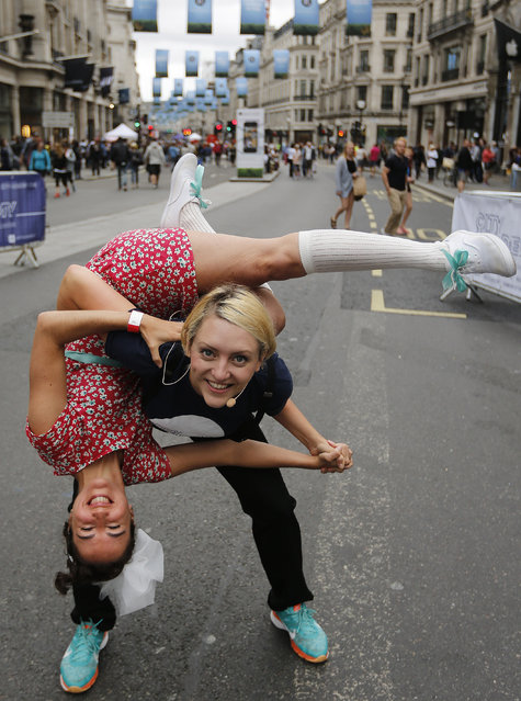 Dancers look at the camera as they perform for the public on the traffic free Regent street in London, Sunday, July 12, 2015, which is normally a busy central city road thoroughfare. Music bands, dance performers and shopping adverts mark the first of this year's traffic-free Summer Streets on Regent Street events. (Photo by Frank Augstein/AP Photo)