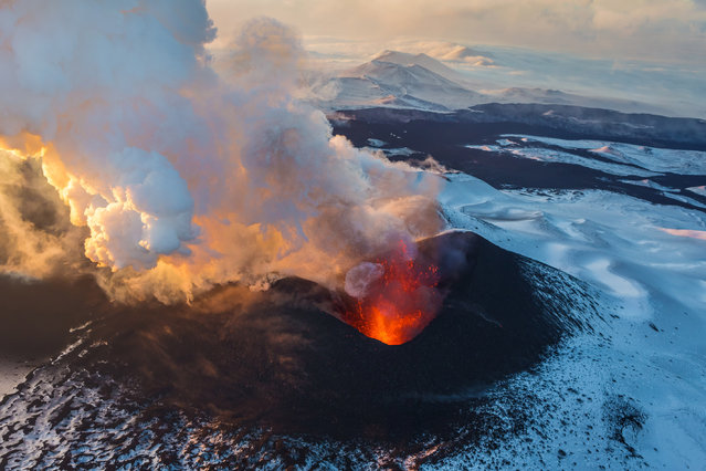 These are the explosive images of some of the world's most ASH-stonishing volcanic eruptions. Spectacular snaps capture lava spewing down the side of Kilauea, ash spitting from craters and plumes of smoke rising thousands of feet in the air. Here: Volcano Plosky Tolbachik, Kamchatcka, Russia. (Photo by Airpano/Caters News)