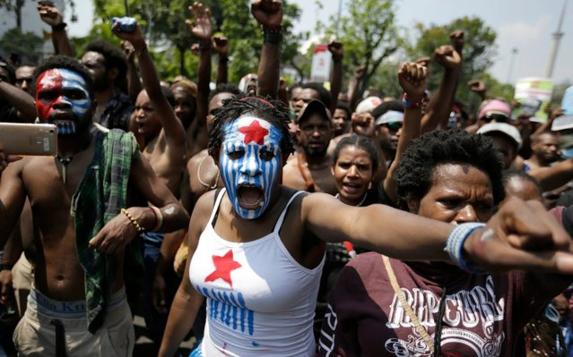 A Papuan activist with her face painted with the colors of the separatist Morning Star flag shouts slogans during a rally near the presidential palace in Jakarta, Indonesia, Thursday, August 22, 2019. A group of West Papuan students in Indonesia's capital staged the protest against racism and called for independence for their region. (Photo by Dita Alangkara/AP Photo)
