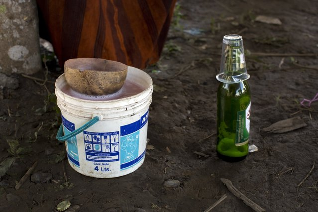 This June 23, 2015 photo shows a bucket filled with the traditional fermented juice of cassava root, known locally as masato, and an empty bottle of Peruvian beer, during celebrations marking the 44th anniversary of the founding of the Otari Nativo village, Pichari, Peru. Masato, which is imbibed throughout the day by community members, including children, is made by boiling the root, chewing it and spitting into a container with water, then left to ferment. (Photo by Rodrigo Abd/AP Photo)