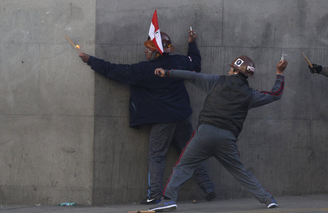 Miners, one wearing a Potosi department flag, launch dynamite sticks, and firecrackers at police during a protest in which Potosi residents are demanding more resources for their region, in La Paz, Bolivia, Friday, July 17, 2015. (Photo by Juan Karita/AP Photo)