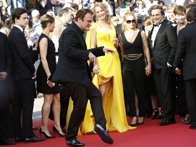 """US director Quentin Tarantino dances as he arrives US actress Uma Thurman (C) for the screening of the film """"Sils Maria"""" at the 67th edition of the Cannes Film Festival in Cannes, southern France, on May 23, 2014. (Photo by Valery Hache/AFP Photo)"""
