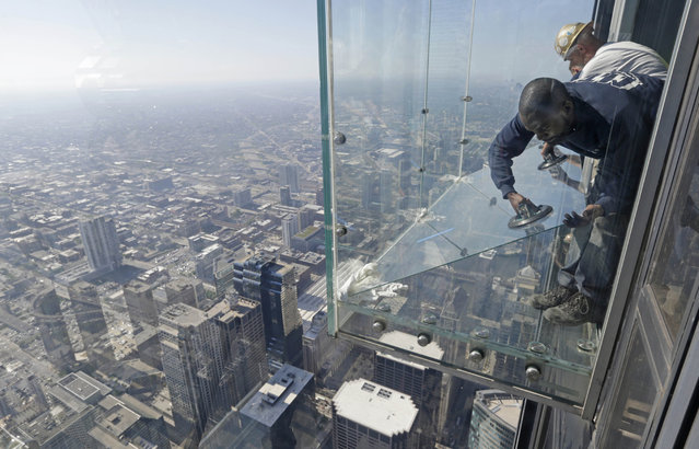 Glaziers from MTH Industries replace a layer of protective coating over the glass surface on the floor of one of four transparent ledges that jut out from the 103rd floor of the Willis Tower in Chicago on May 29, 2014. The see-through glass bays known as The Ledge were designed with a protective coating that completely covers all glass surfaces to protect against scratches. One of the coatings cracked Wednesday night when a family was standing on it. Officials say the family wasn't in danger and the coating does not affect the structural integrity of the enclosure. (AP Photo/M. Spencer Green)