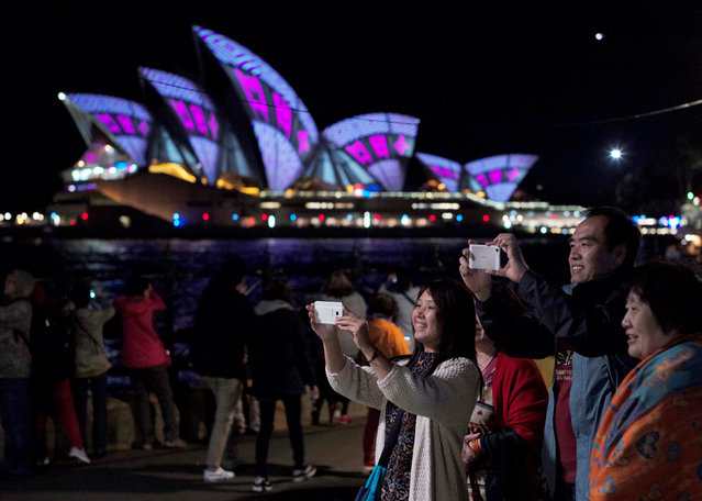 Visitors to the annual Vivid Sydney light festival take pictures as images are projected onto the Sydney Opera House on the second night of the light and sound festival in Sydney, Australia, May 28, 2016. (Photo by Jason Reed/Reuters)