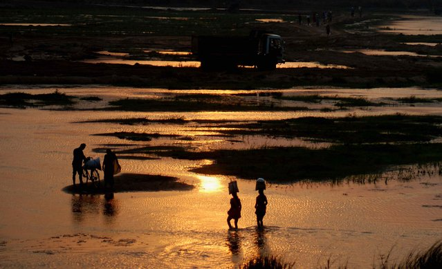 Indian villagers cross the Daya River as they return home after finishing daily marketing on a hot afternoon, on the outskirts of eastern Bhubaneswar on May 19, 2014. (Photo by Asit Kumar/AFP Photo)
