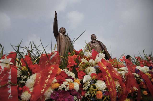 Bronze statues of the late leaders Kim Il Sung, left, and Kim Jong Il tower over flower offerings at Munsu Hill, Monday, July 27, 2015, in Pyongyang, North Korea. North Koreans gathered to offer flowers and pay their respects to their late leaders as part of celebrations for the 62nd anniversary of the armistice that ended the Korean War. (Photo by Wong Maye-E/AP Photo)