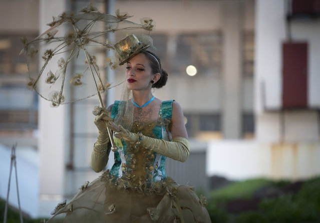 """A model takes part in the """"Trashion"""" fashion show on the roof of a building in the Brooklyn Navy Yard in the Brooklyn borough of New York May 31, 2014. The show featured designers who used recycled items such as coffee filters, tissue paper, grain sacks and window screens. (Photo by Carlo Allegri/Reuters)"""